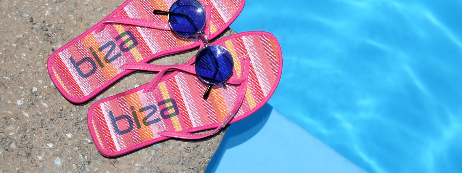 Sandals with the Biza logo on them next to a pool.