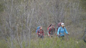people with backpacks walking uphill