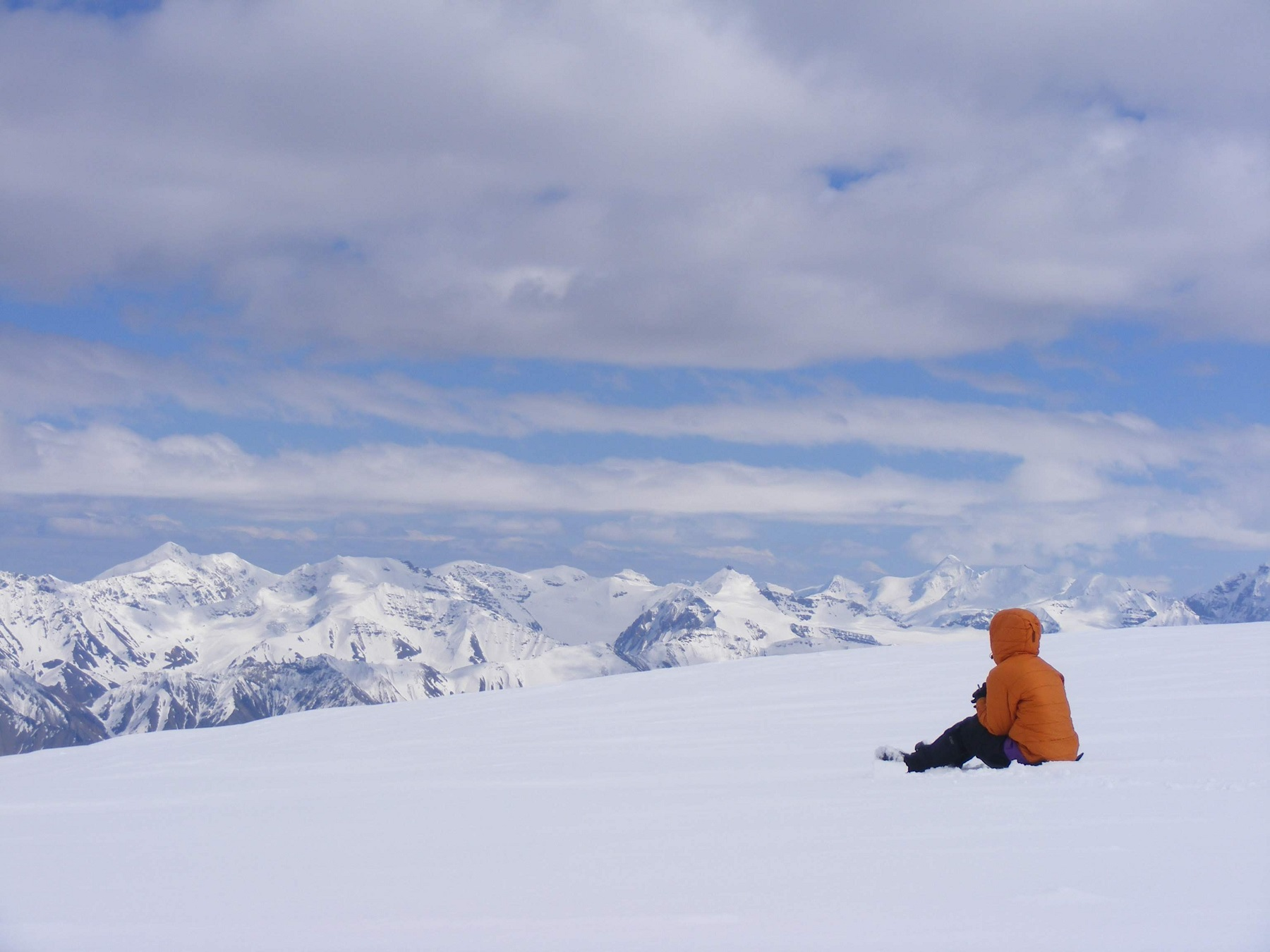 Person in coat on snow looking at snowy mountains