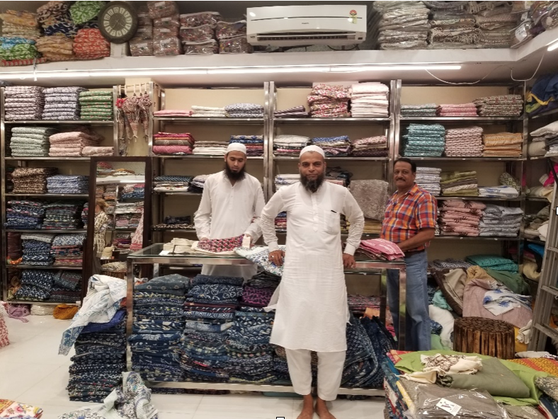 Block print artisans in front of wall of fabric