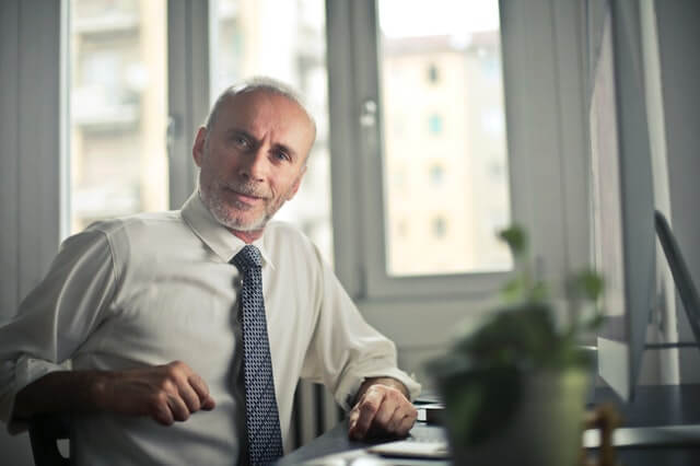 Middle aged man sitting at computer desk