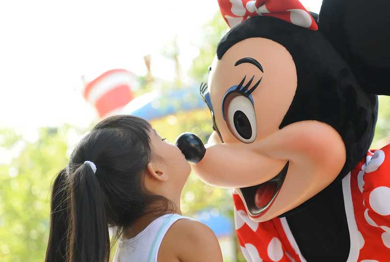 Young child kissing Minnie Mouse on the nose at the Disneyland Resort on a trip booked by Main Street Magic, LLC., a no-fee travel agency specializing in Disney vacation planning   Authorized Disney Vacation Planner