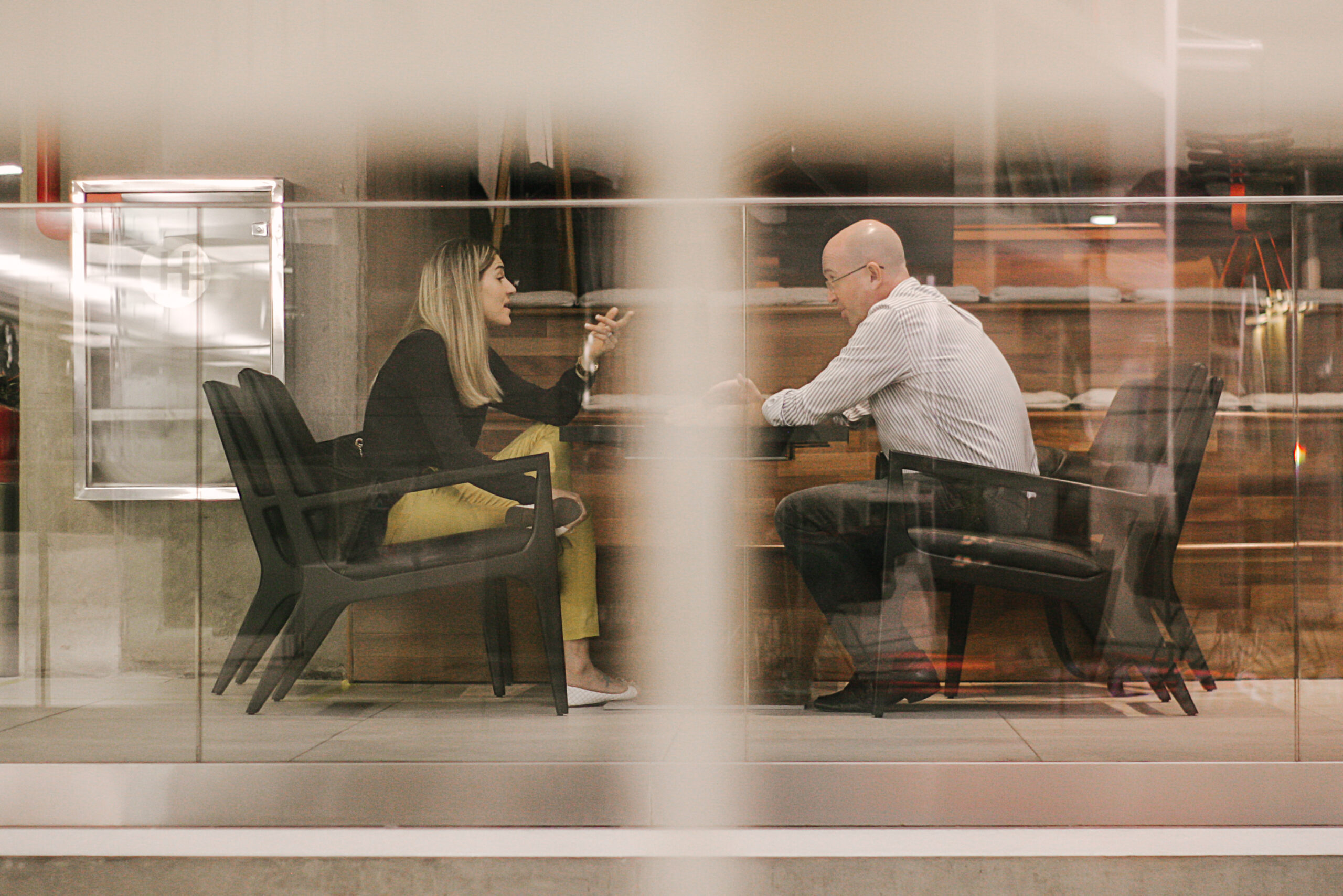 Canva - Man and Woman Sitting on Black Wooden Chairs