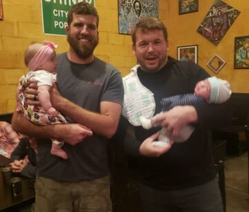 Anthony and Rory holding their babies at company christmas party - nelson & company llc