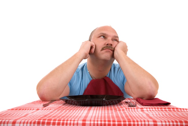 Overweight man looking very unhappy with empty plate in front of him