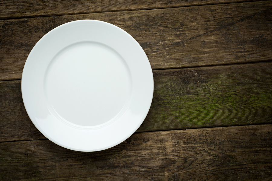 Empty white plate on wooden background close up