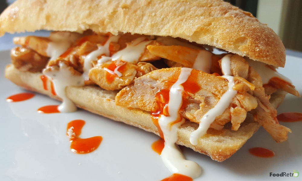 This Crockpot Buffalo Chicken Wing Sandwich is prepped and cooked in just 2 hours. Since you serve straight out of the slowcooker, it's a great choice for tailgate parties! | FoodRetro.com