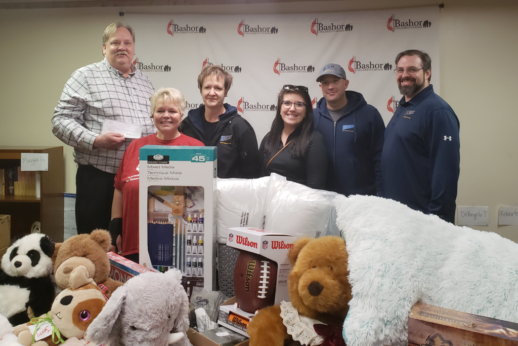 INSERV employees stand behind toys donated to Bashor Childrens Home