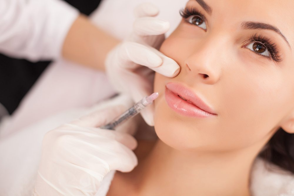 Woman with doctor sticking needle into chin.