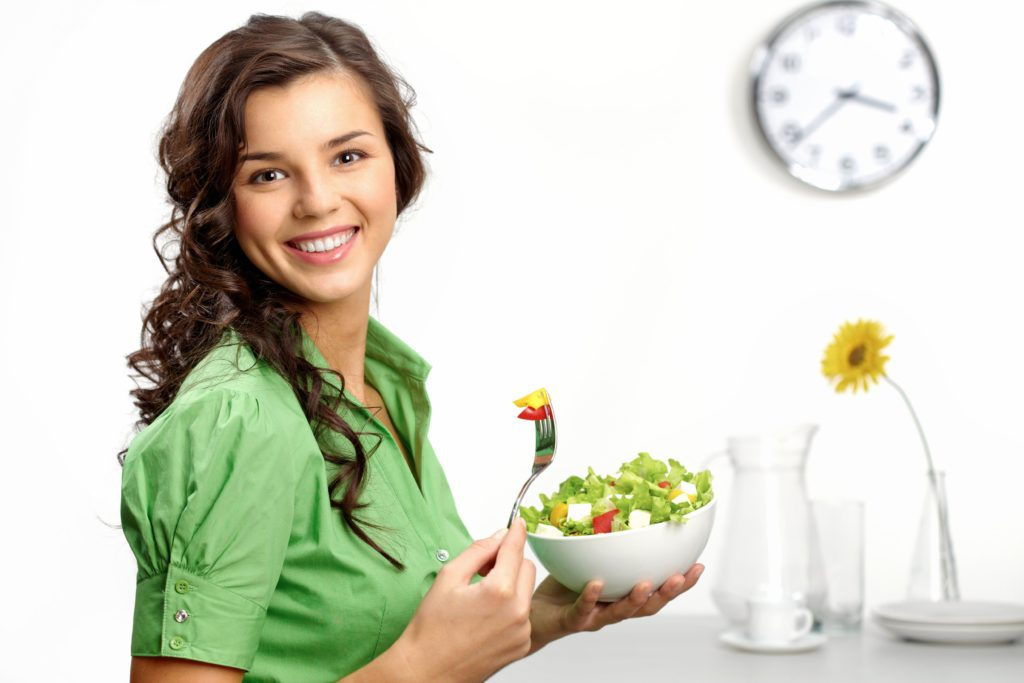 Woman smiling and eating a salad