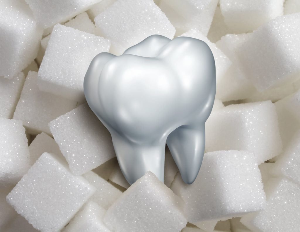 Computerized image of a tooth over a background of sugar cubes