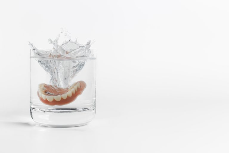 Dentures splashing into a glass of water