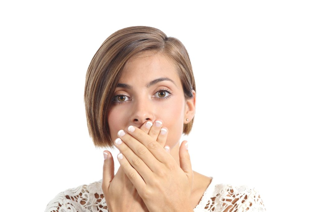 Woman looking ashamed and covering her teeth with her hands