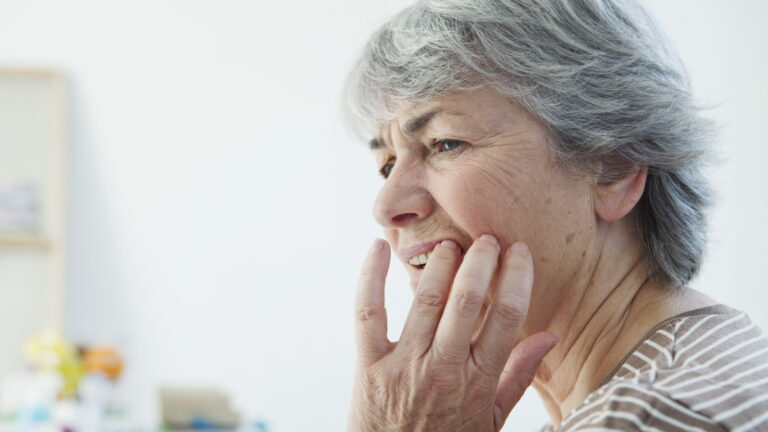 Elderly woman holding side of jaw in pain