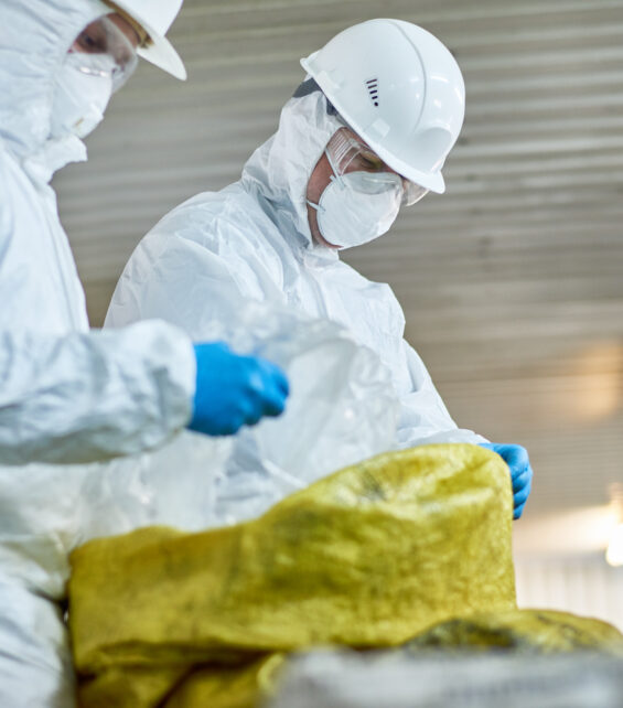 Side view portrait of two workers  wearing biohazard suits working at waste processing plant sorting recyclable plastic on conveyor belt
