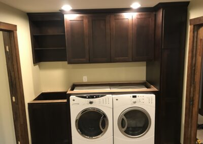 laundry room with dark wood cabinets