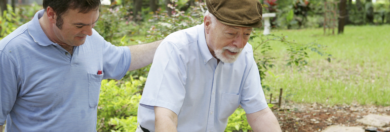 Son or Caregiver Walking Father Using Walker