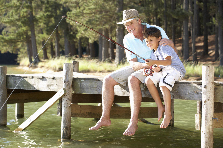 Senior man fishing with grandson