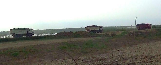 Xe tải chở đất, cát nối đuôi nhau chạy rầm rầm trên hồ Biển Lạc Ảnh: Thanh Niên