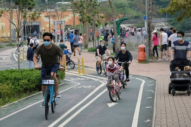 Người dân đeo khẩu trang đạp xe trong đại dịch Covid-19 ở Hồng Kông /// Reuters