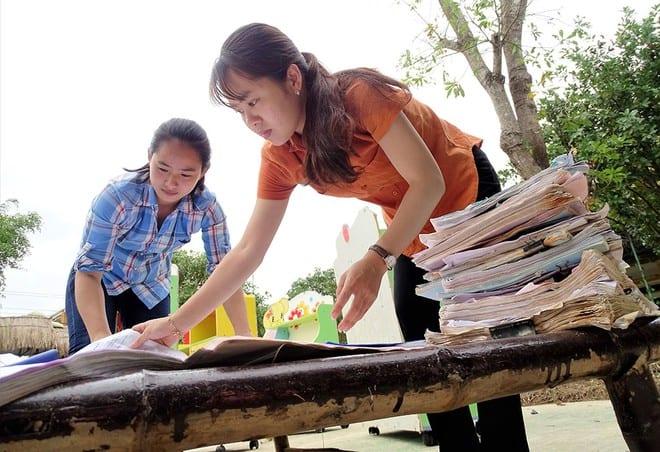 Cô giáo Trường mầm non Phong Bình 2 (Thừa Thiên-Huế) tranh thủ nắng phơi những chồng tài liệu bị ướt, mốc do ngâm lũ /// ẢNH: ĐÌNH TOÀN