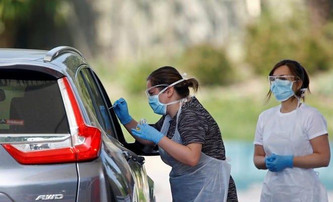 Các nhân viên y tế lấy mẫu xét nghiệm Covid-19 tại London, Anh /// Reuters