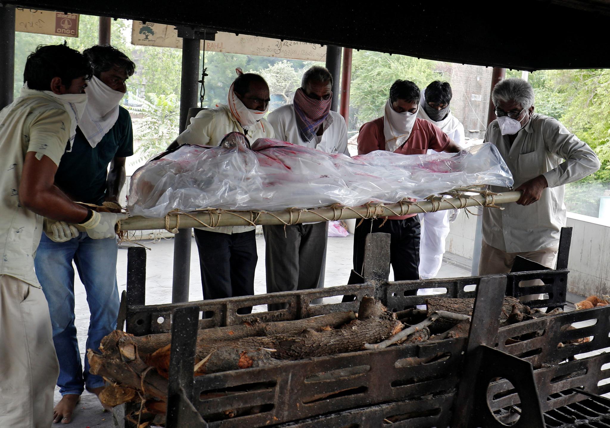 Một số người chuẩn bị hỏa táng người thân chết vì Covid-19 ở thành phố Ahmedabad, Ấn Độ ngày 10.6 /// Reuters