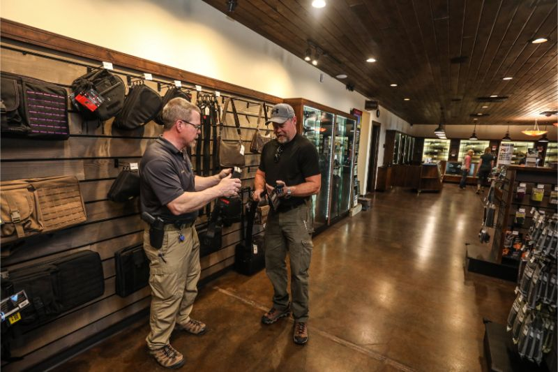 Timberline Firearms employee selling accessories to visitor.
