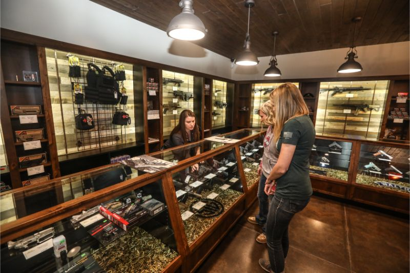 Timberline Firearms employee selling guns to two visitors.