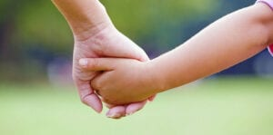 close up of a child holding an adults hand