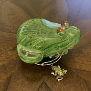 glass frog on top of a bracelet with a frog charm