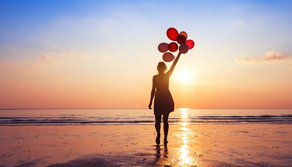girl with balloons at sunset