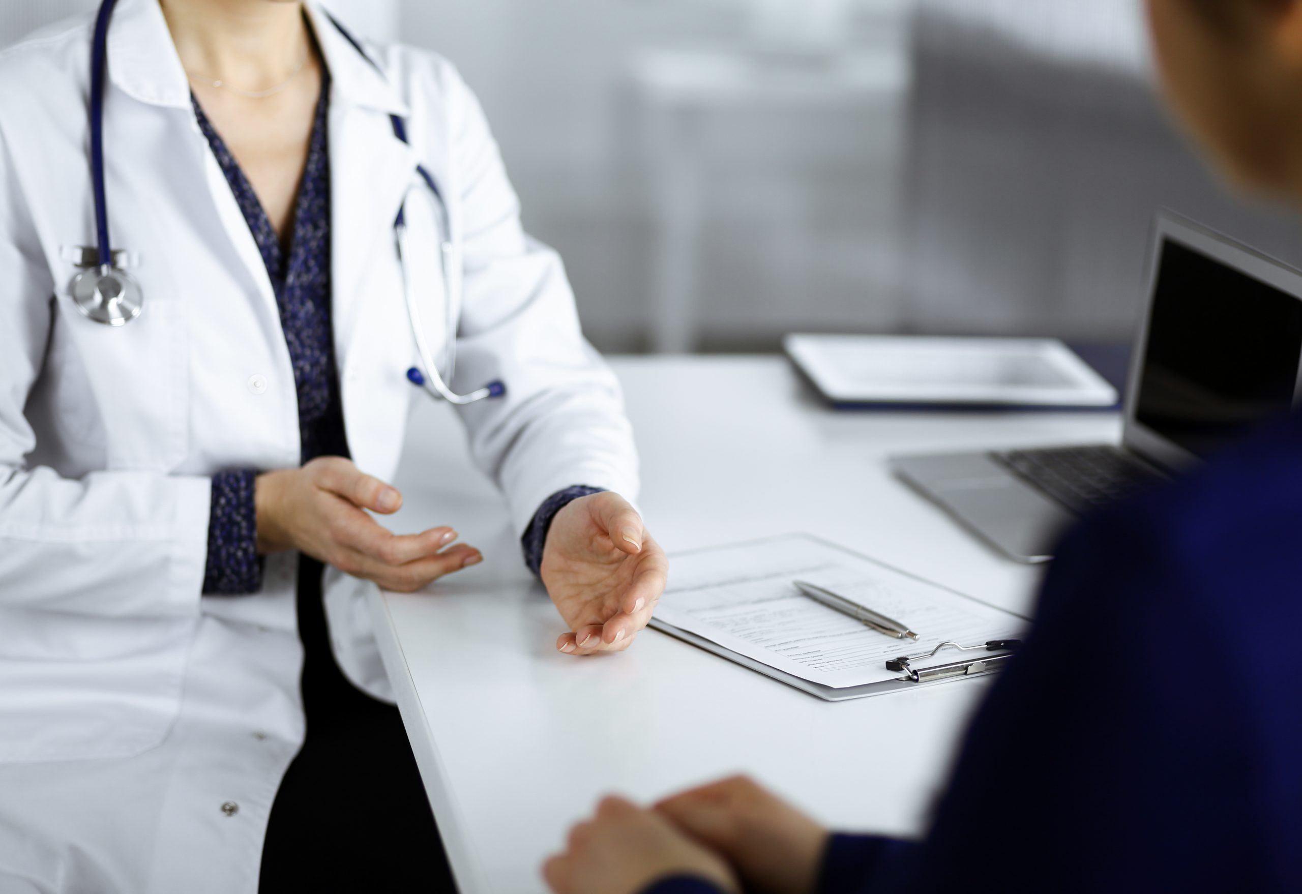 Unknown woman-doctor is talking to her patient about her diagnosis, while sitting together at the desk in the cabinet in a clinic.