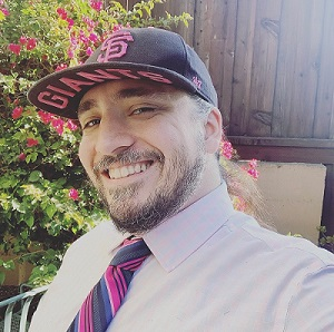 Young white man with beard and St Louis ball cap wearing a pink-striped tie.