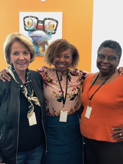 Lynda and two other women standing together, arms over each other. CMT's mission
