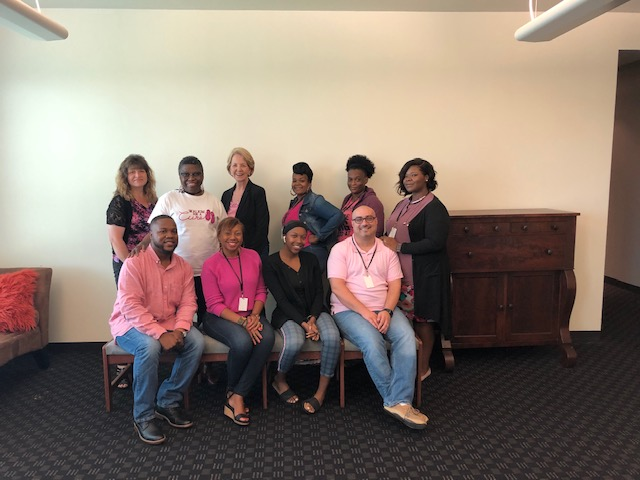 Posed group employees in the Orlando office wearing pink.