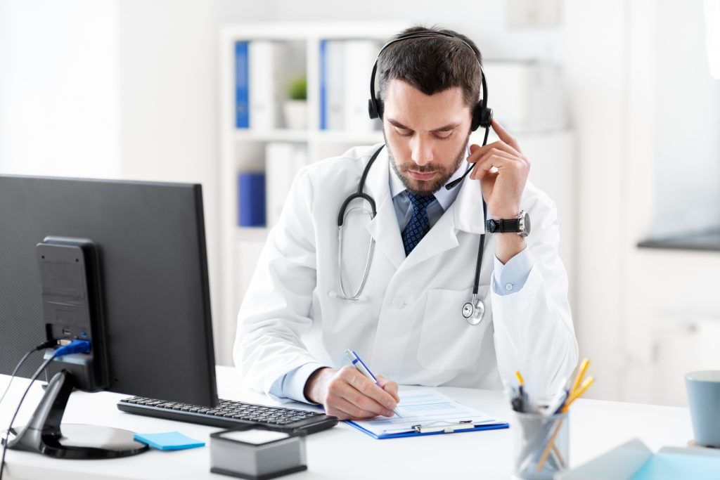 male doctor with headset and clipboard at hospital working on laboratory patient access.