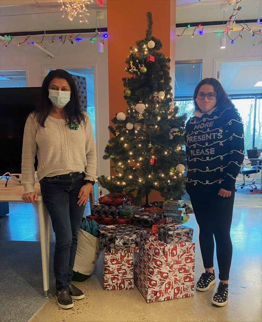 Two women standing on each side of a Christmas tree with presents stacked underneath it.