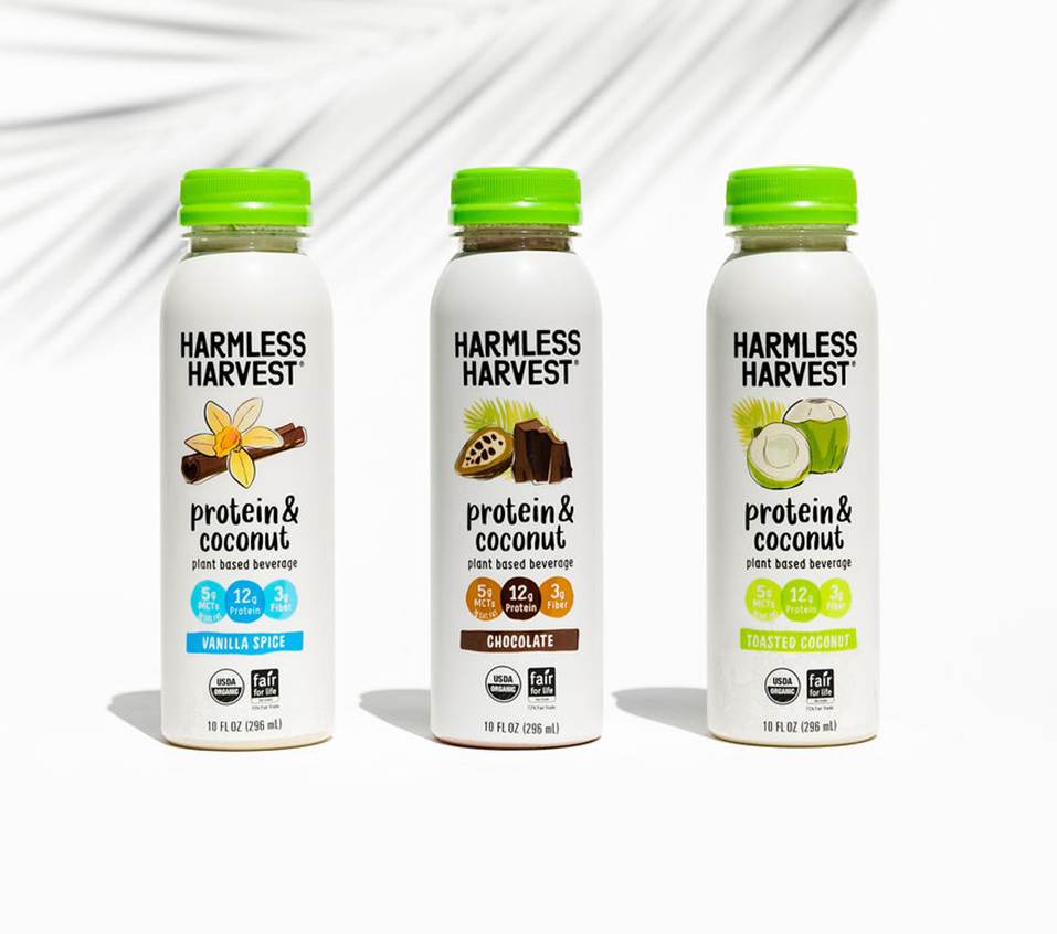 Front view of the Harmless Harvest Protein & Coconut 10oz bottle line, all flavors w/ a palm front shadow in the background