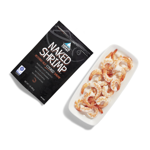 Cooked Naked Shrimp in a one pound black retail bag next to a plate of fresh cooked shrimp with tails on sitting on a plate.