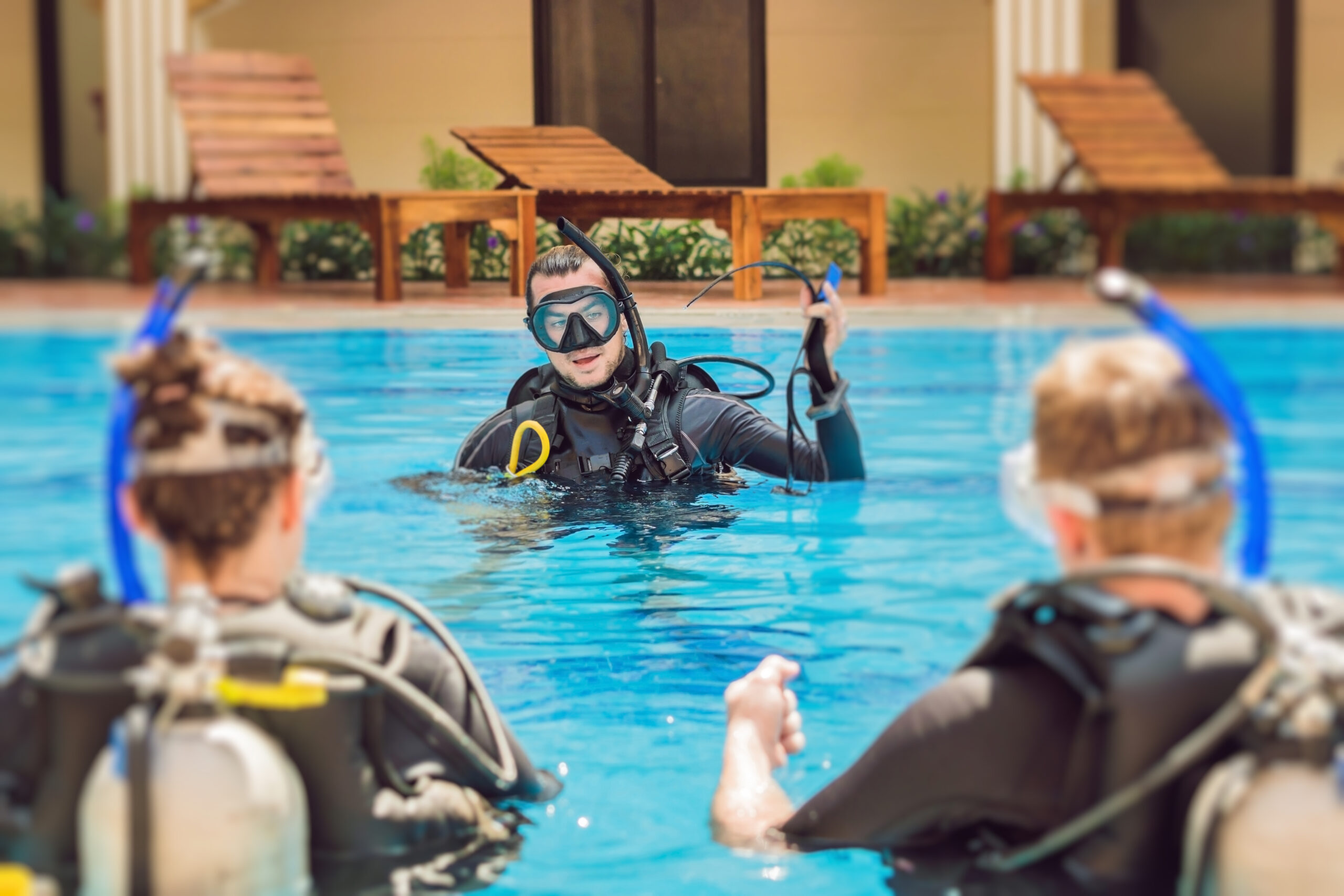 Diving instructor and students. Instructor teaches students to dive.