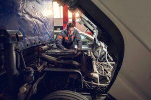 Mid adult mechanic repairing a truck in auto repair shop.