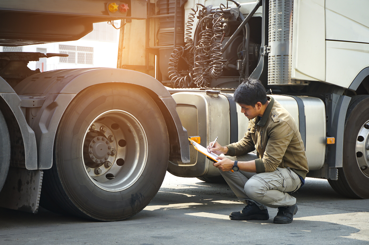 Asian truck driver holding clipboard inspecting safety vehicle maintenance checklist a truck wheels, tire