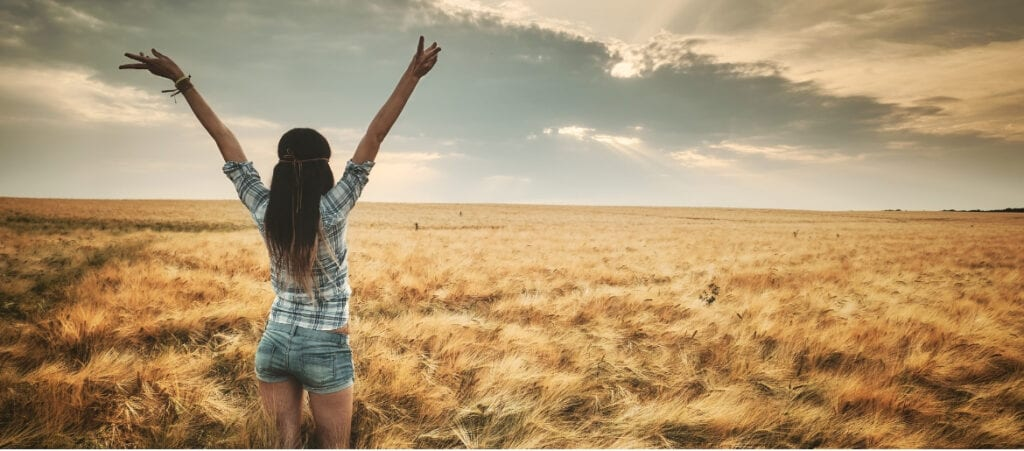 woman raising her arms feeling worthy of the sun on her face