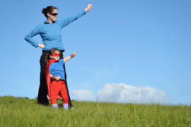 courageous parent and girl standing in the grass posing like a superhero