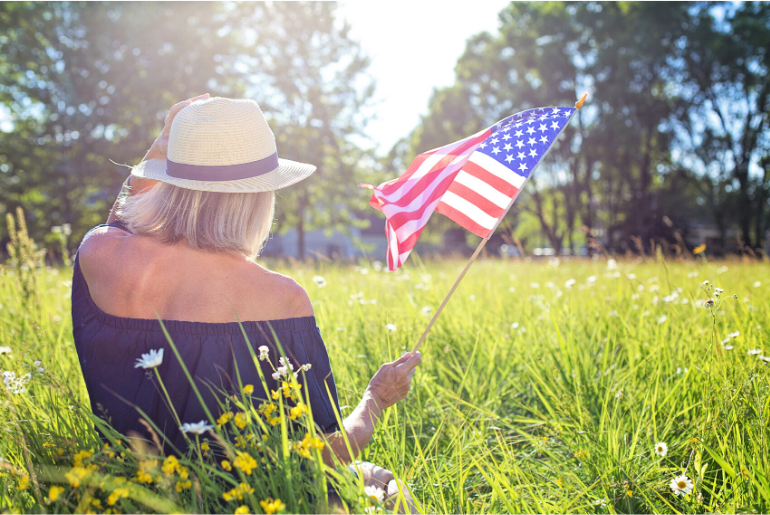 woman in grass waving American flag