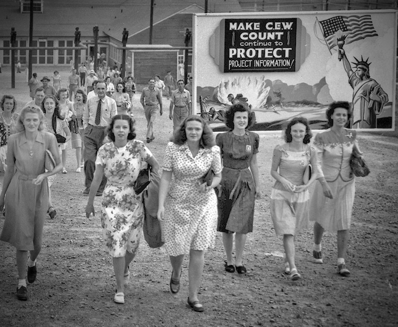 """Shift change at the Y-12 uranium enrichment facility in Oak Ridge, Tennessee, during the Manhattan Project. Notice the billboard: """"Make CEW count — Continue to protect project information."""""""