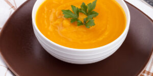 Pumpkin soup in a bowl on white wooden table