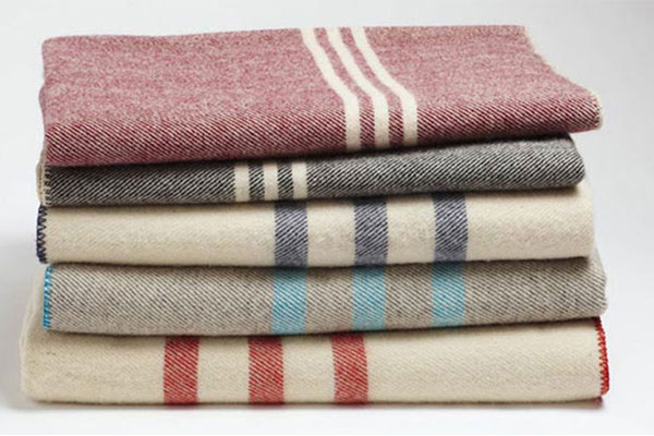Stack of striped wool blankets by Coyuchi