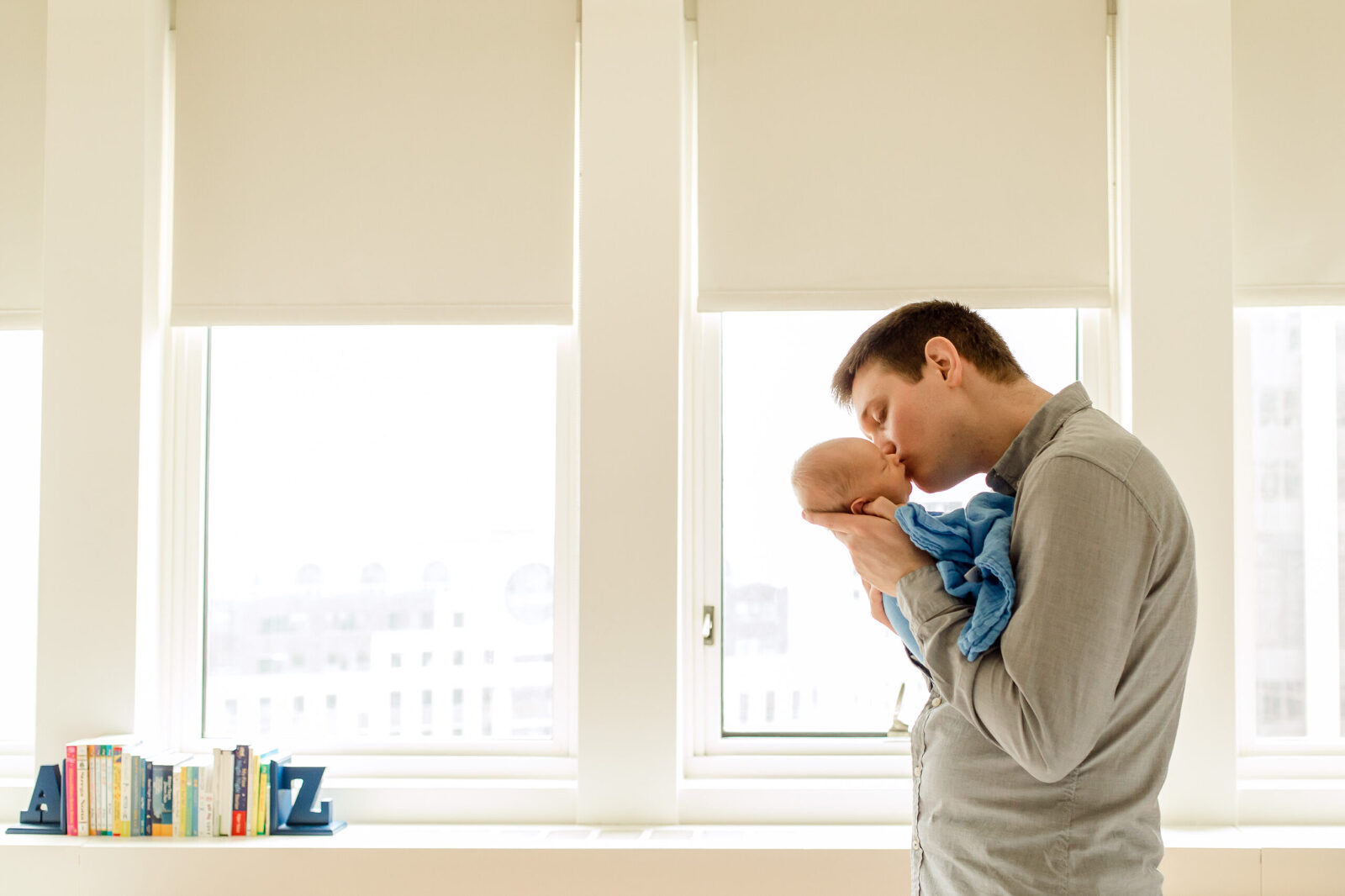 dad kisses his new baby in front of sunlit windows